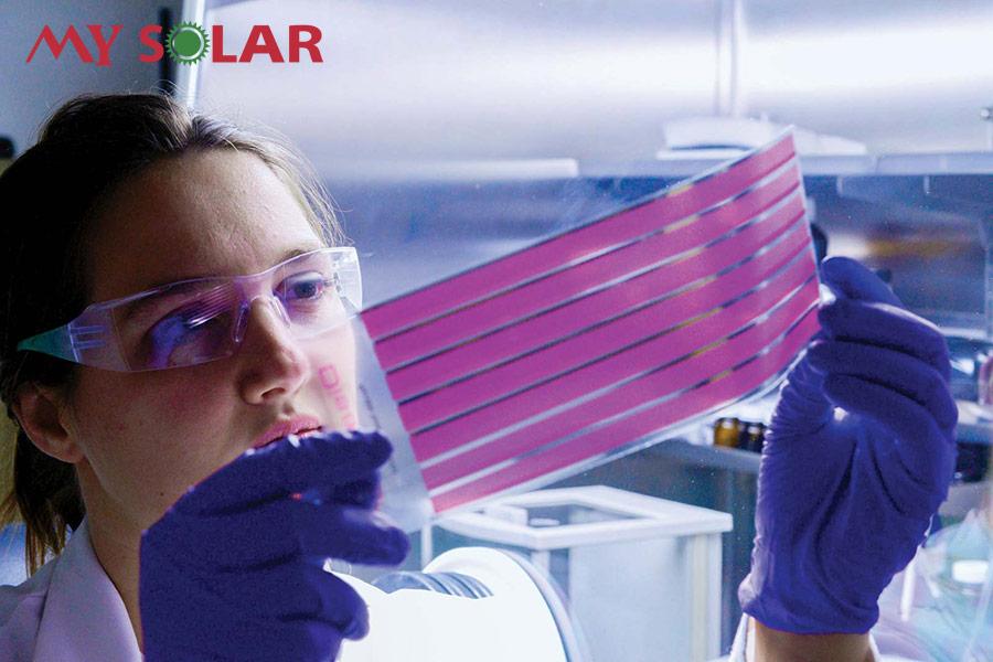 Một nhà khoa học đang kiểm tra tế bào pin năng lượng mặt trời